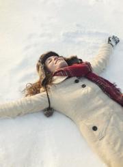 happy woman lying in snow